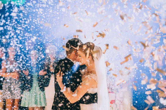 結婚式の二次会パーティ。ゲストに囲まれる紙吹雪の中の新郎新婦。